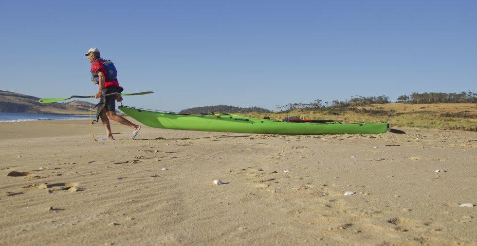 Ein Mann zieht ein Kajak über den Strand ans Wasser