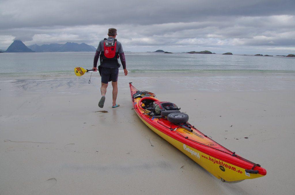 Im Vordergurnd ein Kajak auf dem Strand