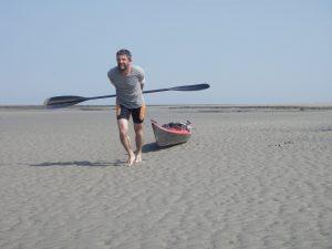 Ein Mann zieht sein Kajak über eine Sandbank