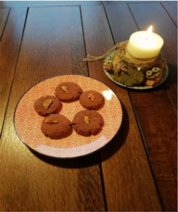 Schokoladenplätzchen auf einem Teller, eine Kerze im Hintergrund