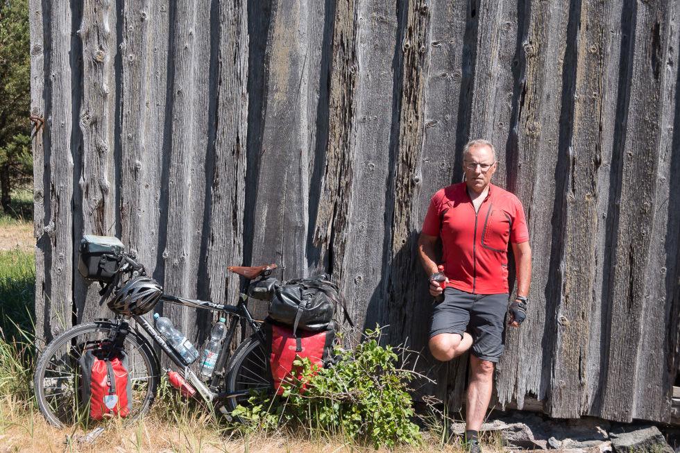 Fahrrad und Mann lehnen an einer Bretterwand